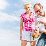 Family romping on field with parents carrying child